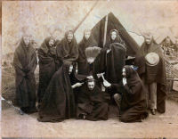 "CABINET CARD PHOTOGRAPH OF 9 INDIAN WAR SOLDIERS WEARING/DRAPING BLANKETS OVER THEIR HEADS, STANDING AND SEATED IN FRONT OF THEIR TENTS, 2 OF THE MEN ARE ""SCALPING"" ANOTHER USING A CAPTURED TOMAHAWK AND HAND SCYTHE."
